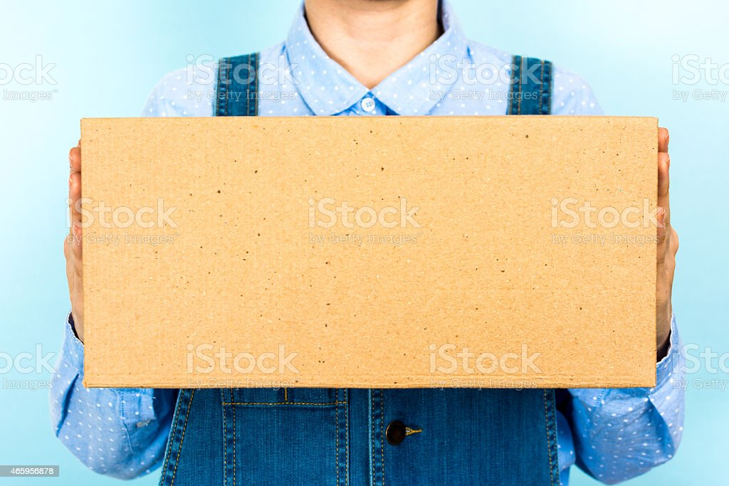 Woman wearing overalls holding blank box, container, cardboard, front view. stock photo