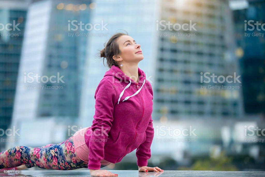 Woman wearing pink sportswear in upward facing dog pose stock photo