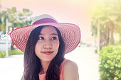 woman wearing pink straw hat with expression of happy