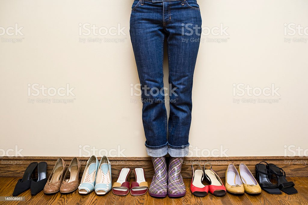 Woman stands in purple plaid rain boots with high heel shoes lined up...