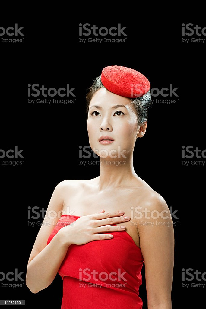 Woman wearing red hat, hand on chest stock photo