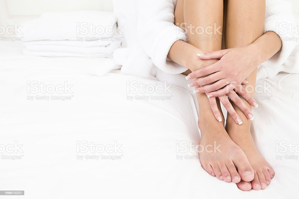 Woman wearing robe sitting on bed stock photo