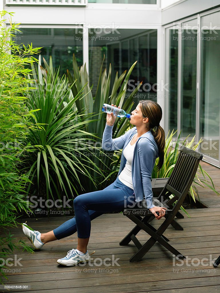 Woman wearing running clothes sitting on garden chair drinking water stock photo