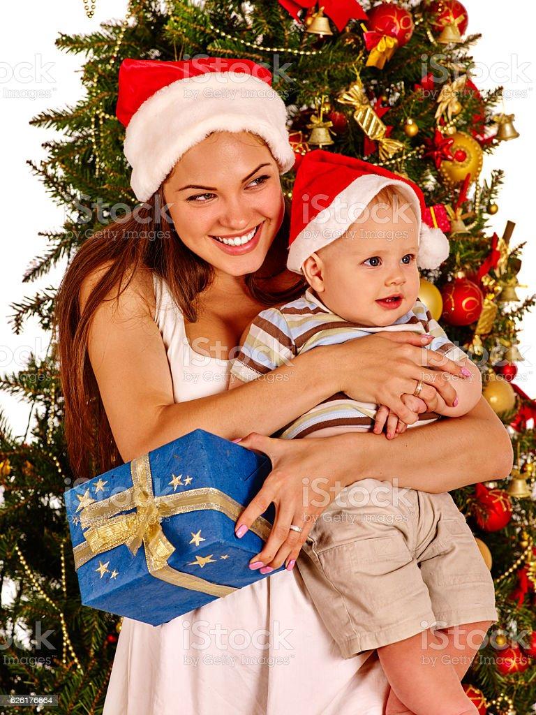 Woman wearing Santa hat holding baby under Christmas tree. stock photo