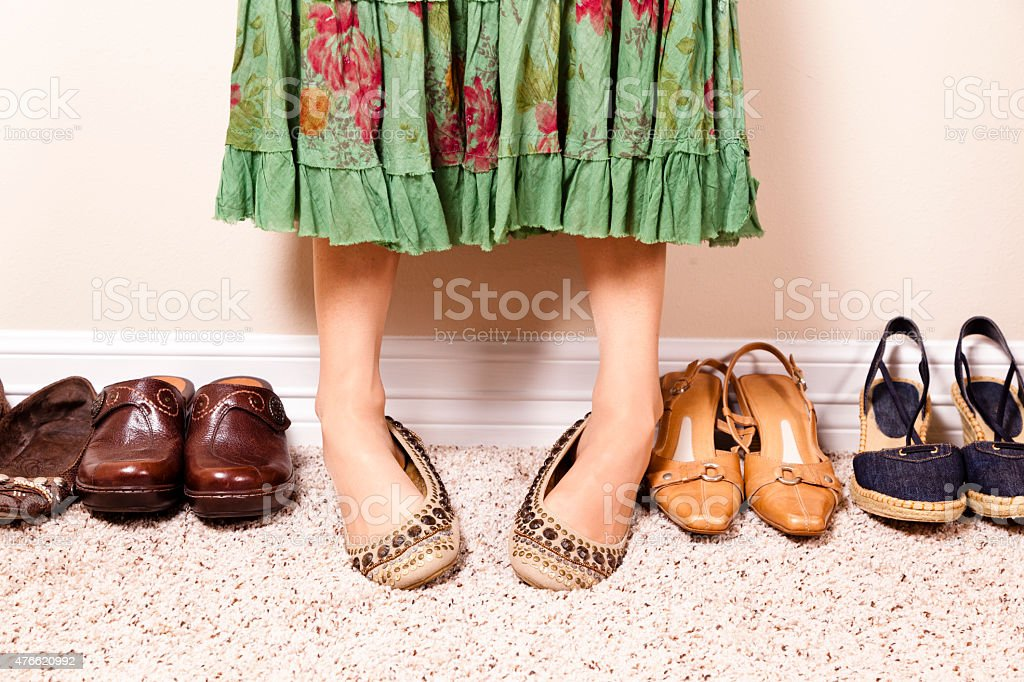 Woman wearing skirt and flat shoes. Shoes line wall. Shopping. stock photo