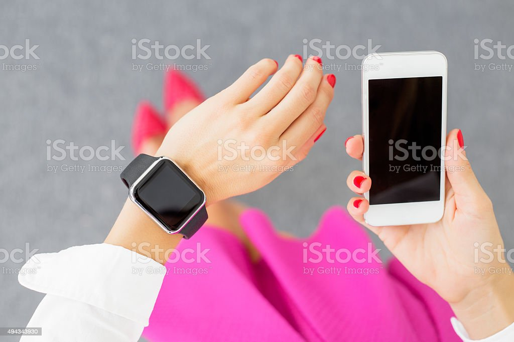 Woman wearing smartwatch and holding cellphone stock photo