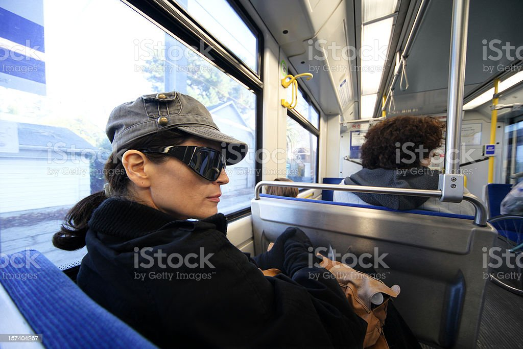 Woman Wearing Sunglasses On Public Transportation royalty-free stock photo
