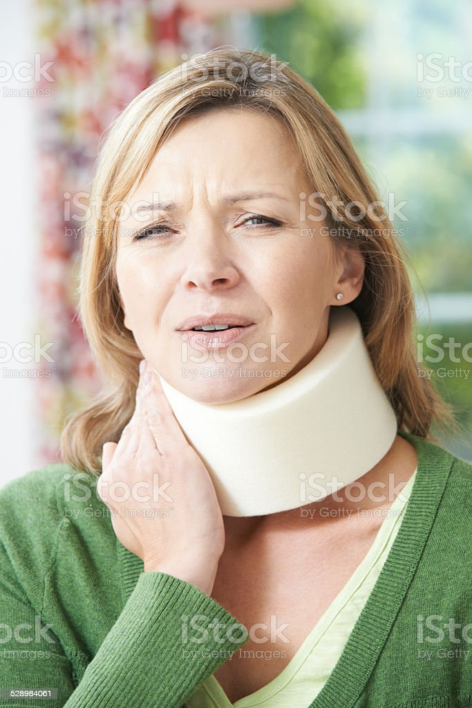 Woman Wearing Surgical Collar In Pain stock photo