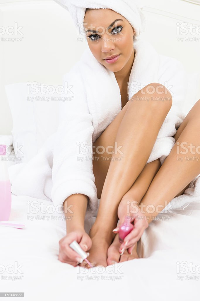 Woman wearing towel painting toe nails royalty-free stock photo