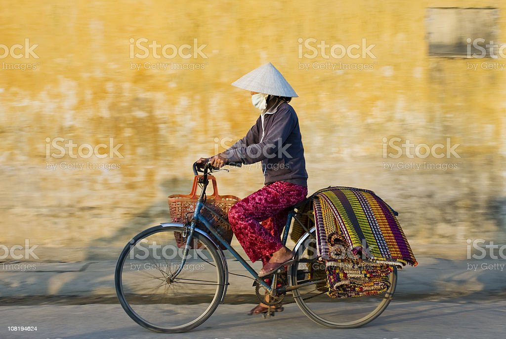 Woman Wearing Traditional Dress in Vietnam Riding Bicycle stock photo