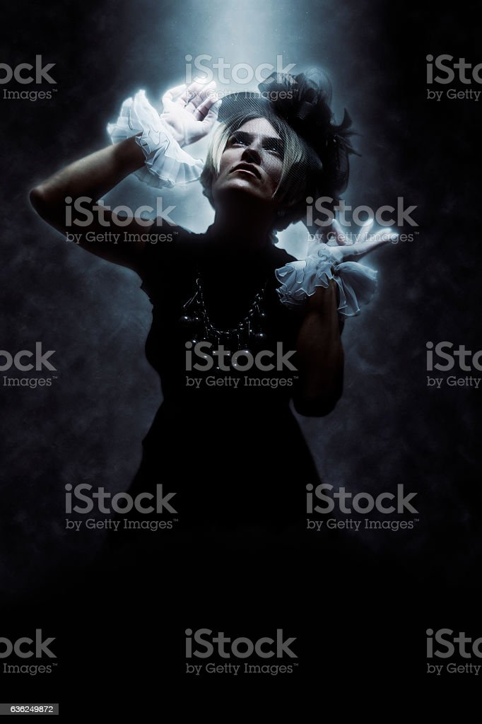 Woman Wearing Vintage Clothes with Dramatic Lighting stock photo