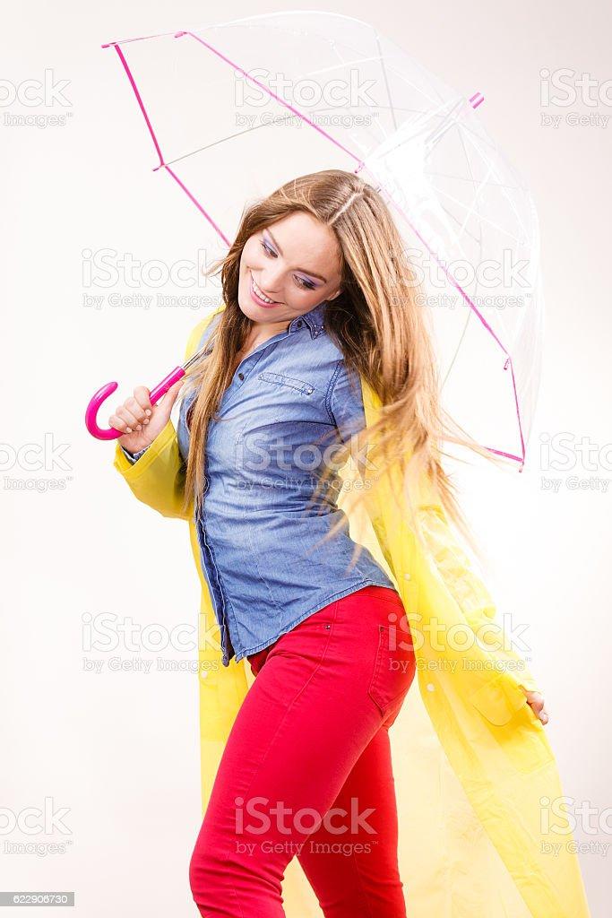 Woman wearing waterproof coat under umbrella stock photo