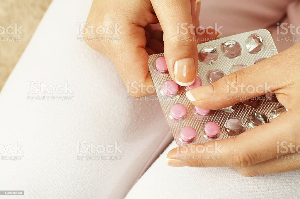 Woman wearing white pants taking pink pills stock photo