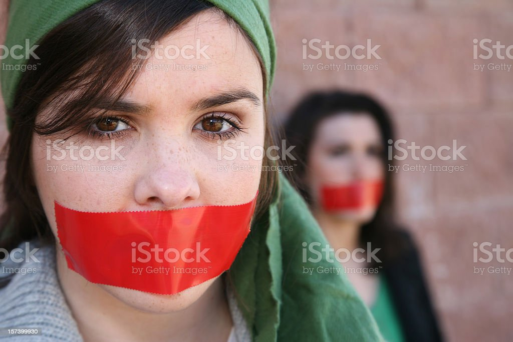 Woman Wearring A Head Scarf With Red Tape On Mouth stock photo