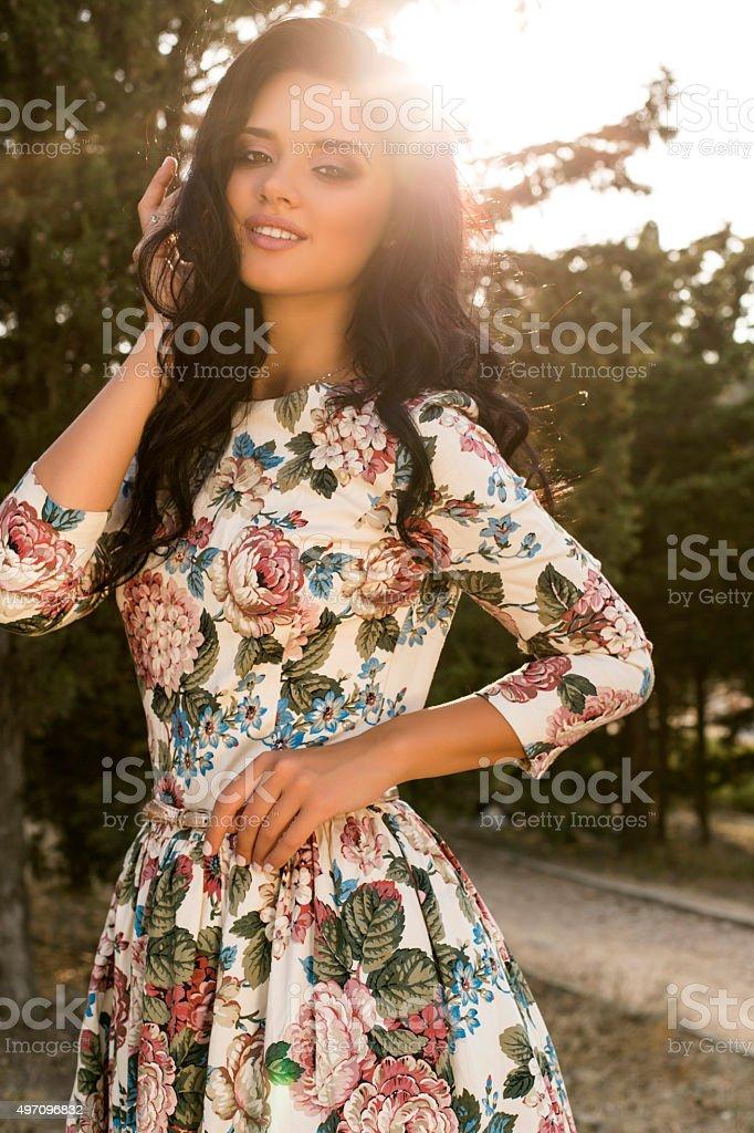 woman wears luxurious colorful dress posing in summer field stock photo