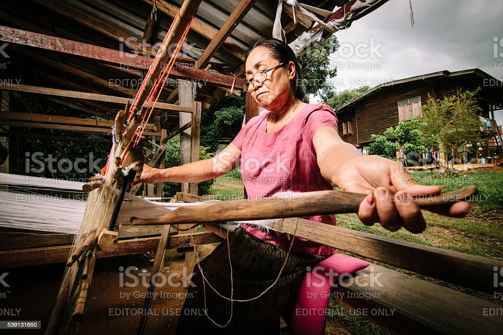 Woman weaves fabric. stock photo