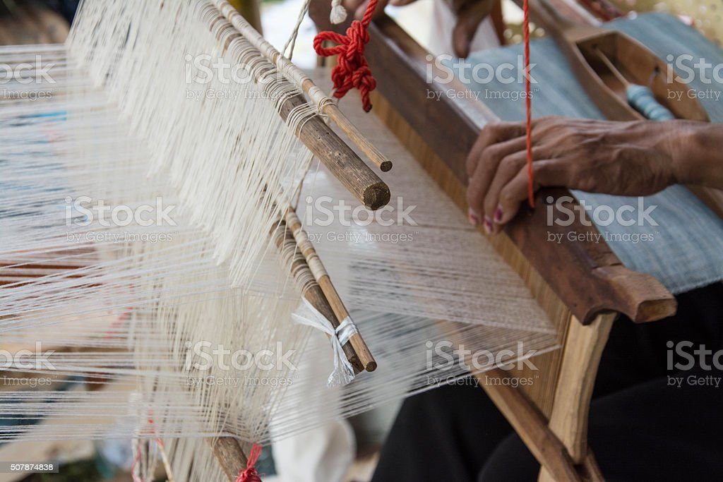 Woman weaving silk in traditional way at manual loom. Thailand stock photo