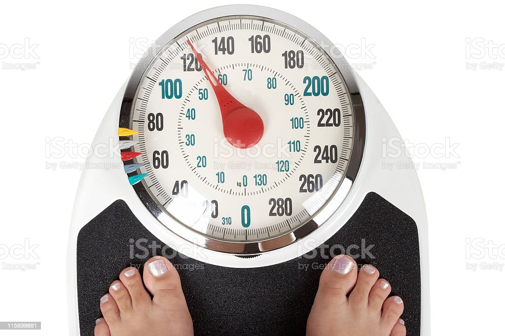 A woman weighing herself on bathroom scales stock photo