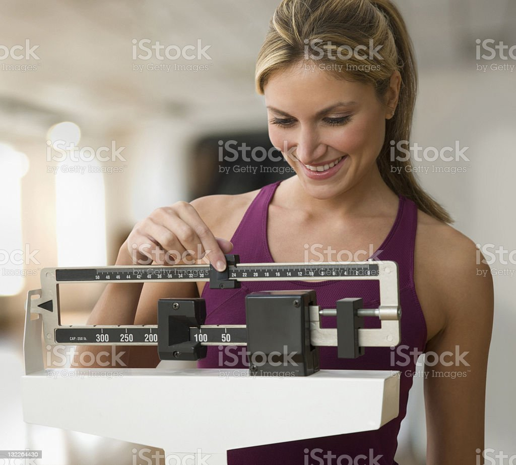 Woman weighing herself stock photo