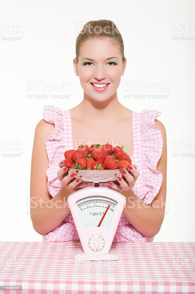Woman weighing strawberries royalty-free stock photo