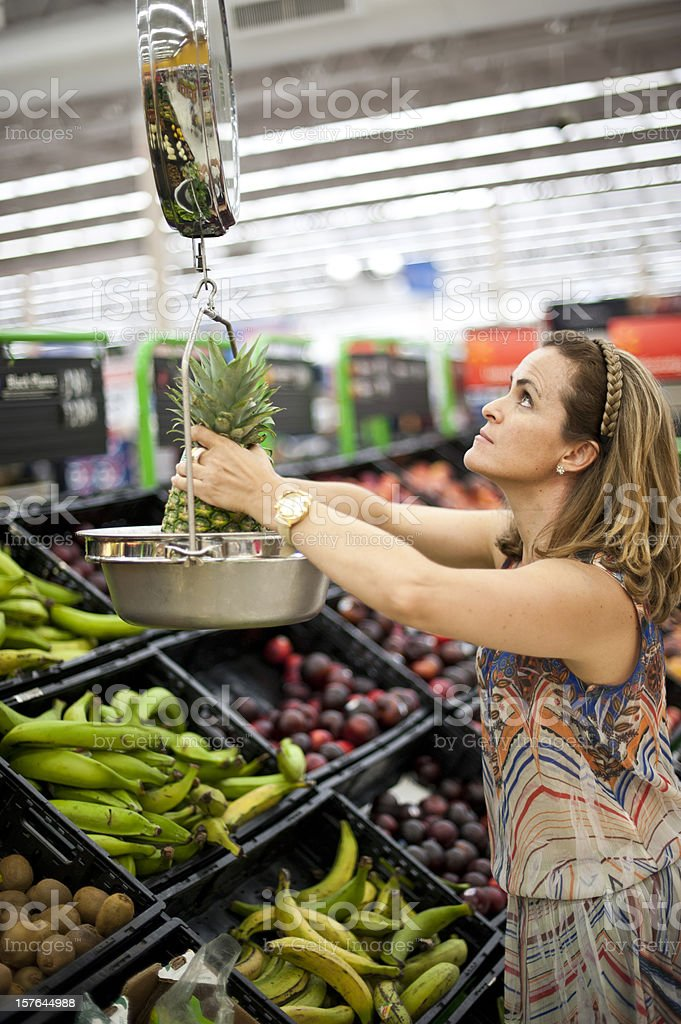 Woman weighting a pineapple royalty-free stock photo