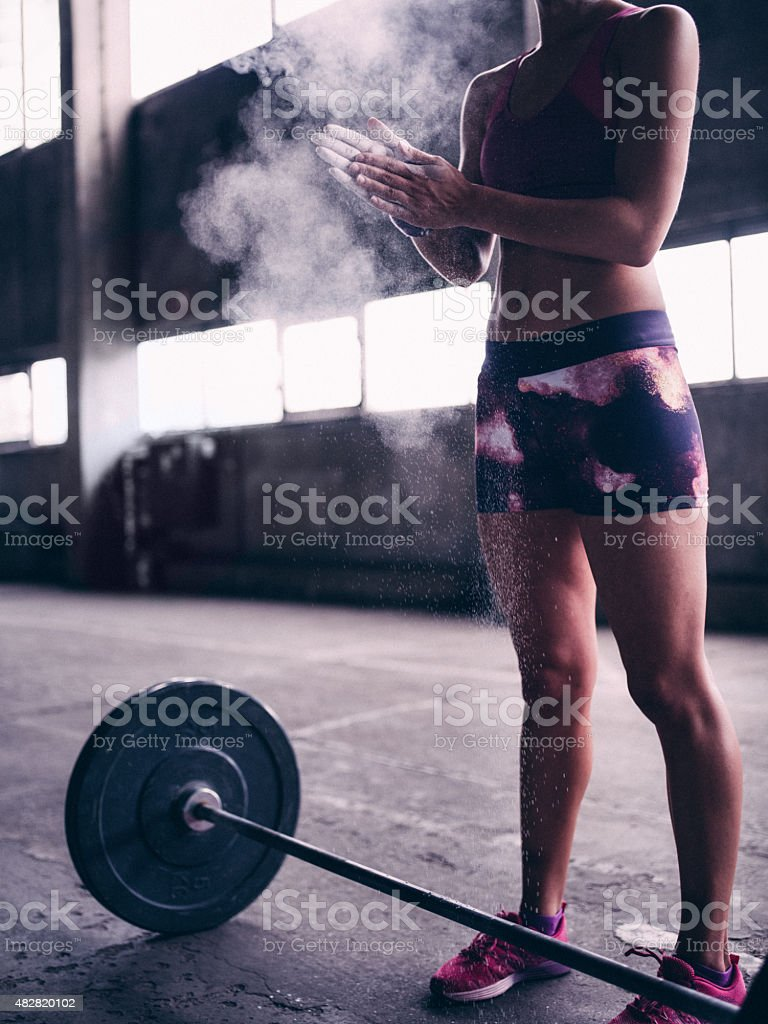 Woman weight-lifter clapping powder from her hands stock photo