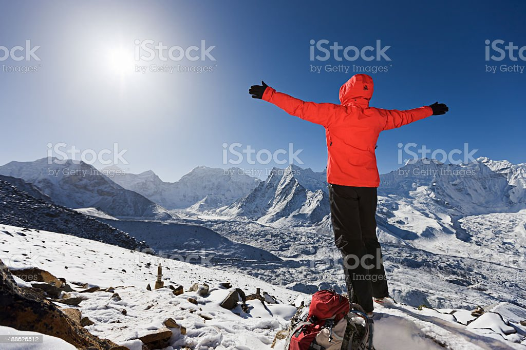 Woman welcoming sunrise on a mountain, Mount Everest National Park stock photo