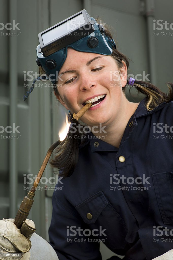 Woman Welder Lighting a Cigar With Her Torch. royalty-free stock photo