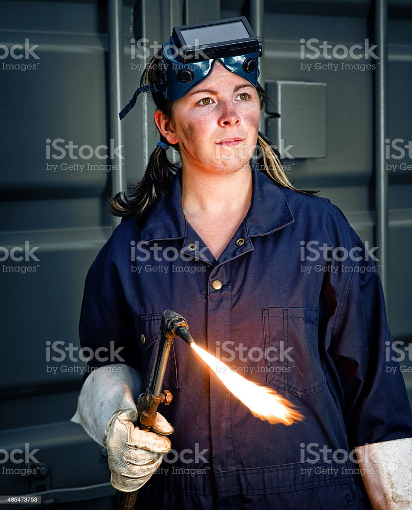 Woman Welder with a Flaming Torch stock photo