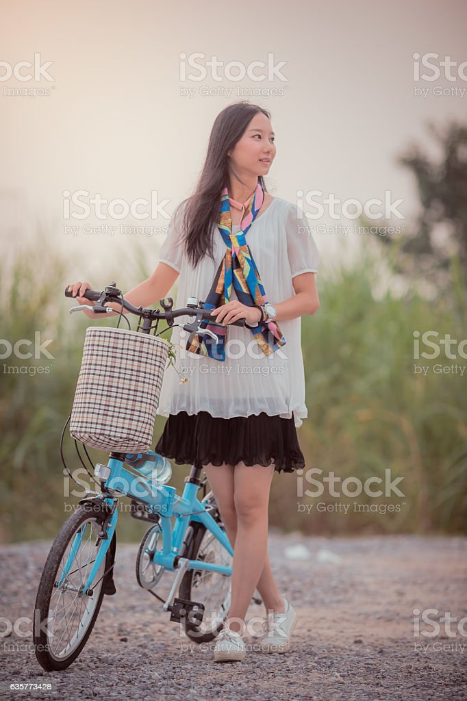 Woman Wheeling A Bike At Sunset stock photo