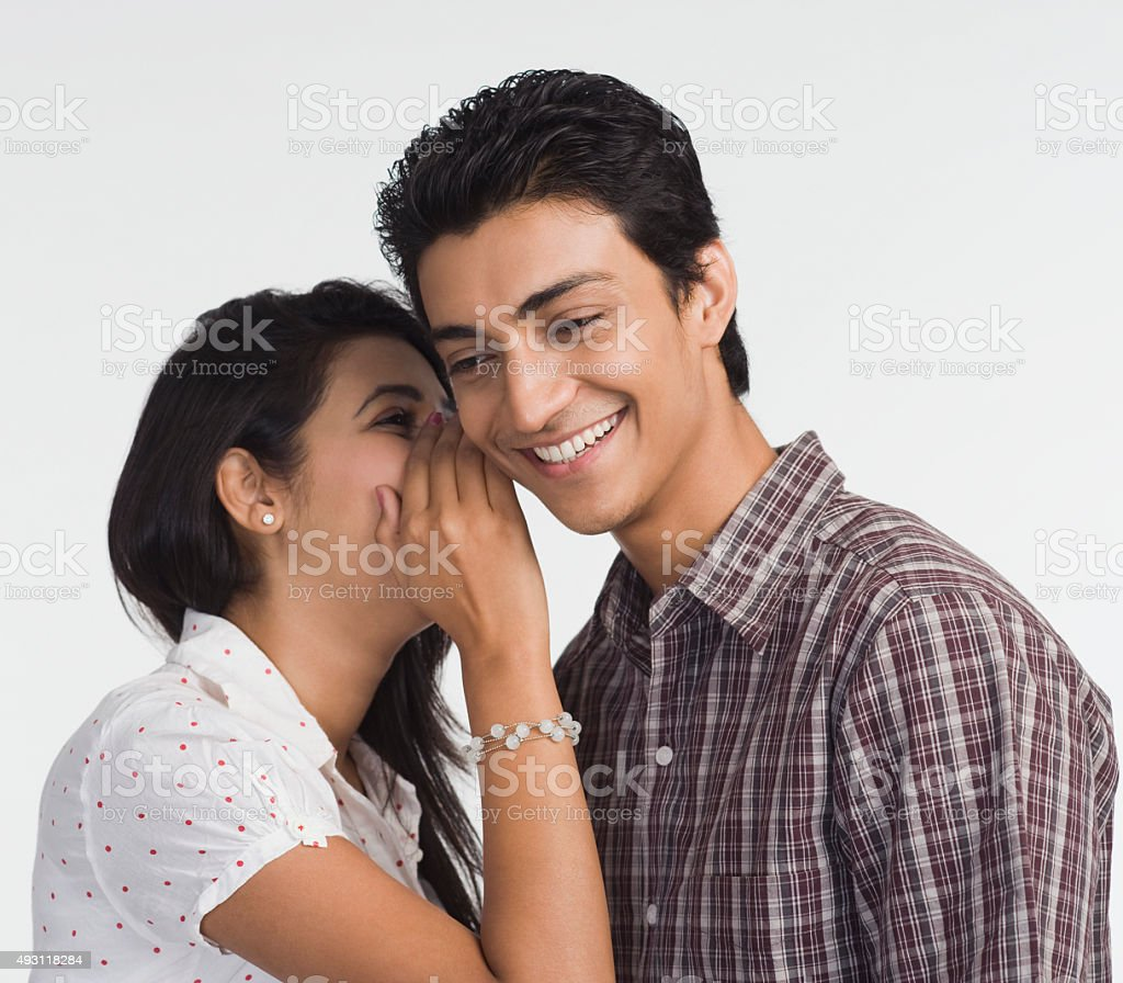 Woman whispering to a man stock photo