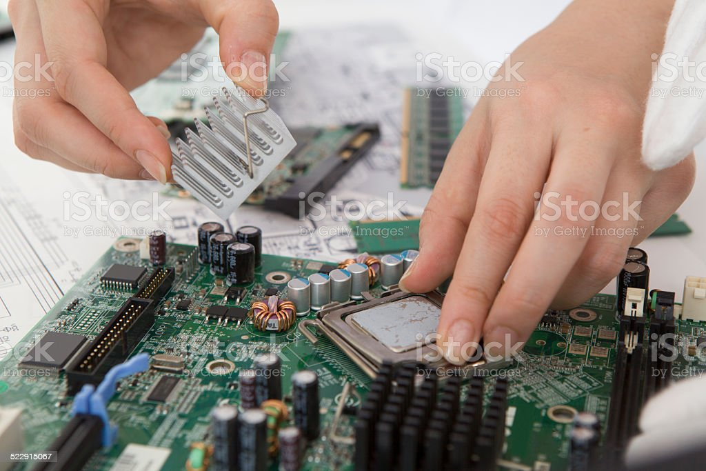Woman who assemble the circuit board by hand stock photo