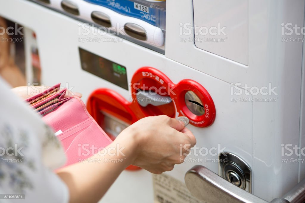 woman who buys water with a vending machine on midsummer days stock photo