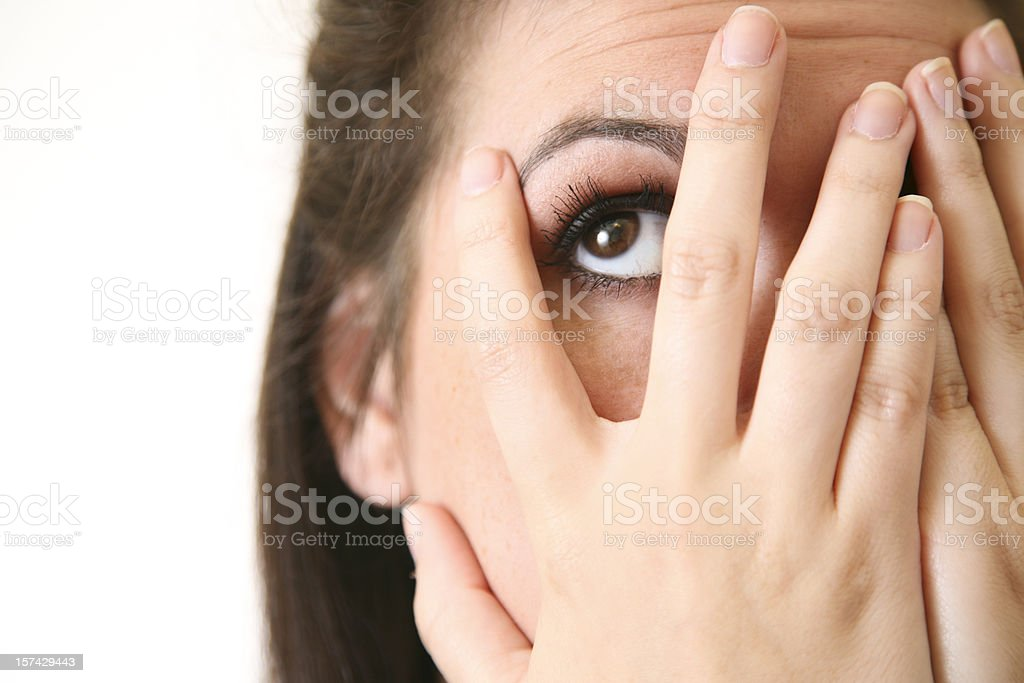 A woman who can not bear to watch peeks through her fingers. royalty-free stock photo