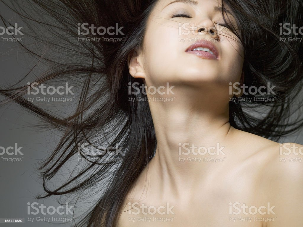 Woman who closed her eye which shakes hair loose stock photo