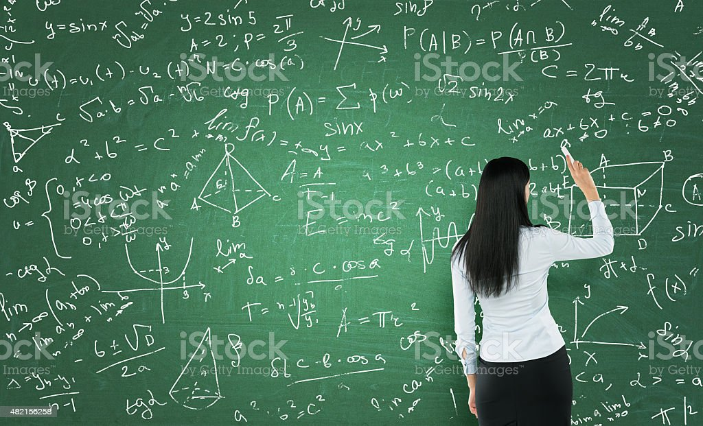 woman who is writing math calculations on green chalk board. stock photo