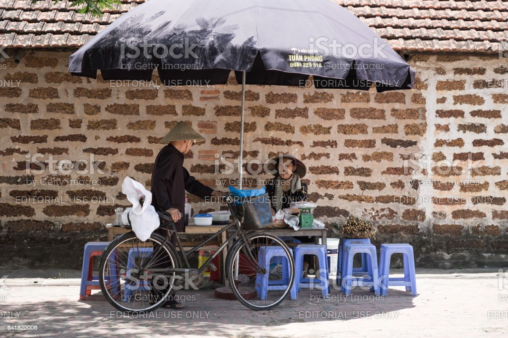 Hanoi, Vietnam - July 16, 2916: Woman who sales stewed fruit, sweetened porridge at stall talking to old man, old brick on background, in Duong Lam ancient village, Son Tay district stock photo
