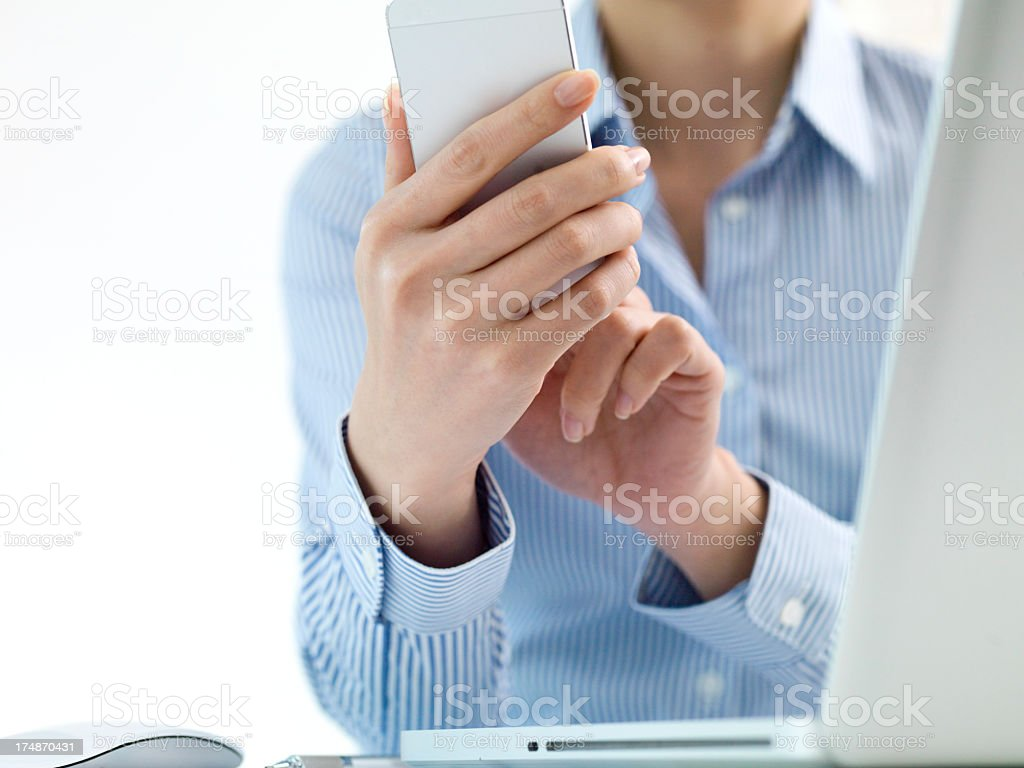 Woman who touches a smartphone in front of notebook PC royalty-free stock photo