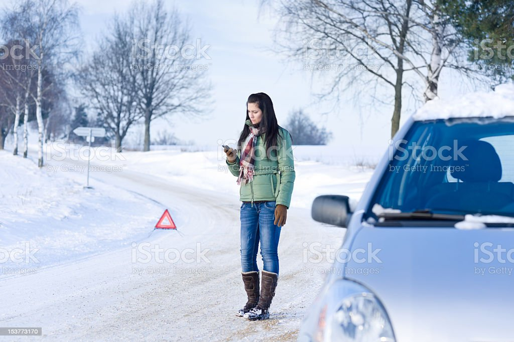 A woman who's car broke down in the winter calling for help stock photo