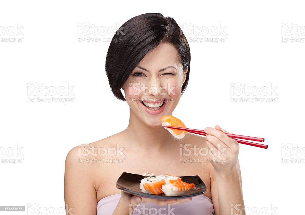 Woman winking and smiling while eating sushi with chopstick stock photo