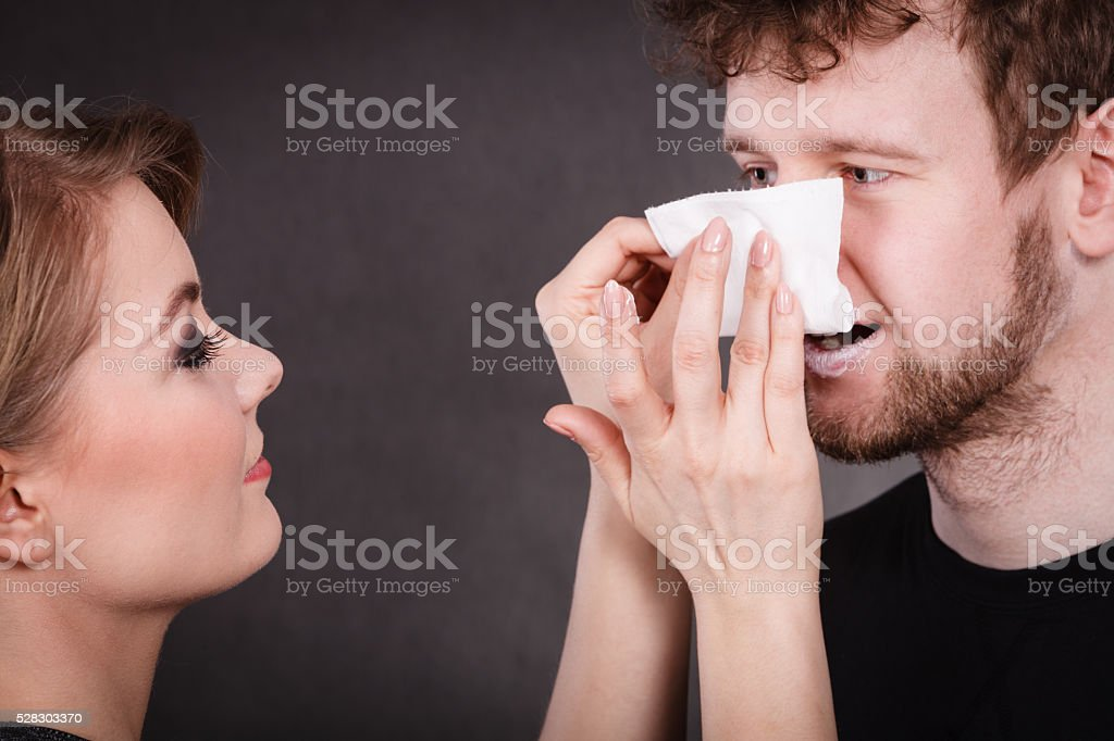 Woman wipe man face by hygienic tissue. stock photo