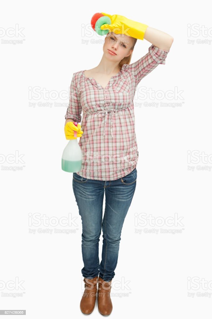 Woman wiping her forehead while holding a spray bottle stock photo