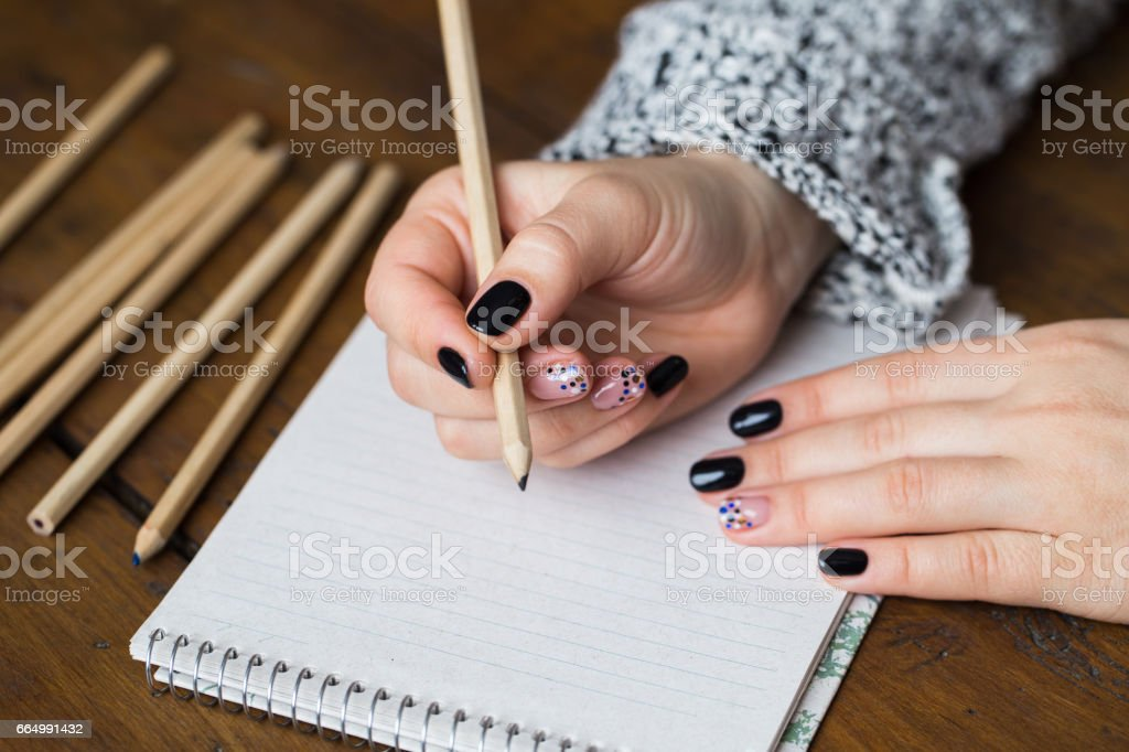 A woman with a beautiful manicure draws in a notebook stock photo