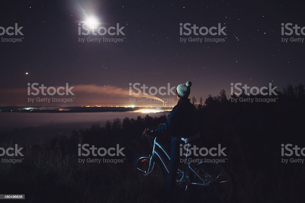 Woman with a bicycle looking at the night landscape stock photo