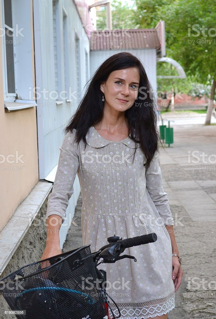 Woman with a bicycle on the street stock photo