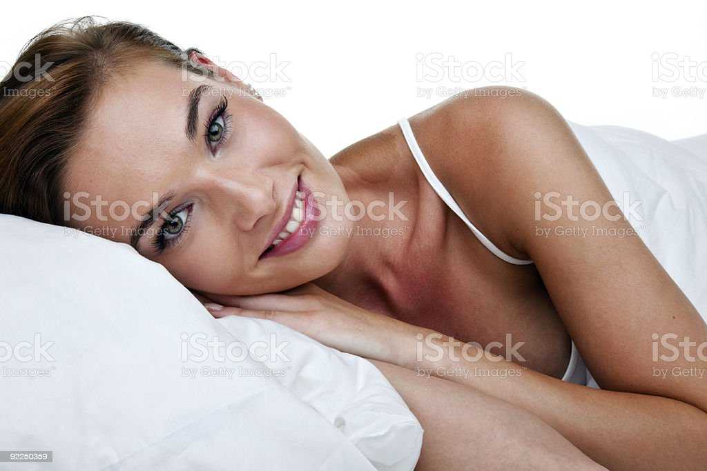 Woman with a big smile laying in bed royalty-free stock photo