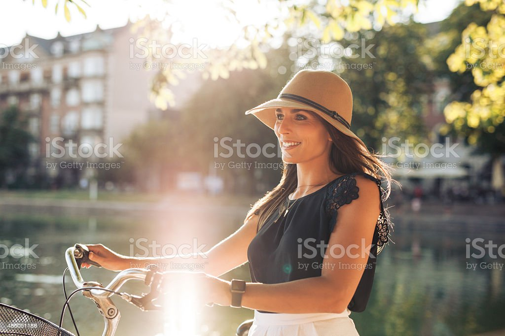 Woman with a bike at city park stock photo