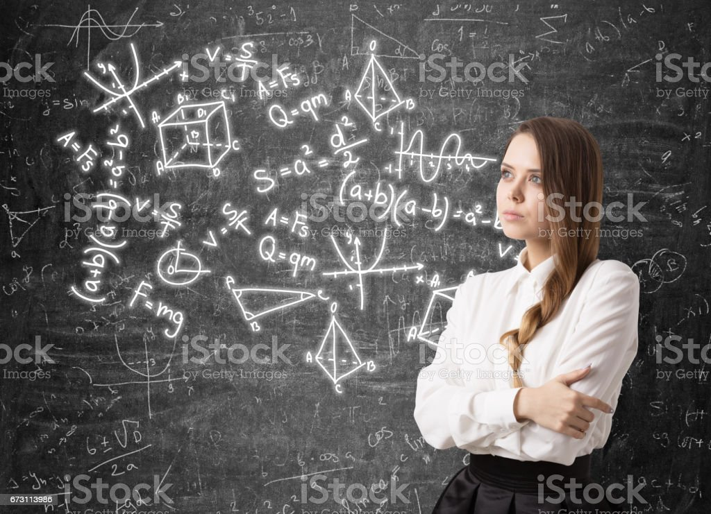 Woman with a braid and formulas on blackboard stock photo