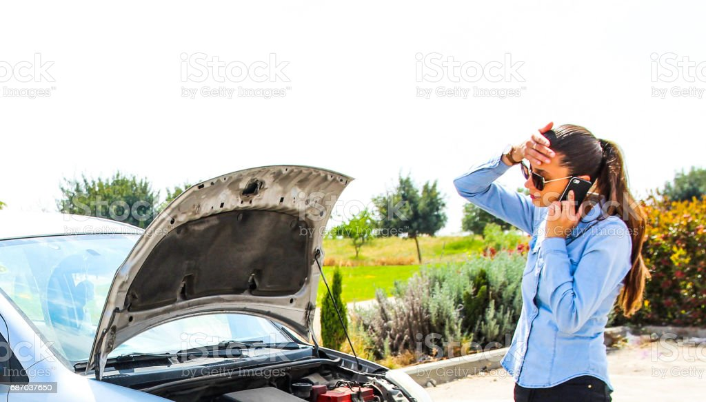 A woman with a broken car she holds her head talking on the phone and...