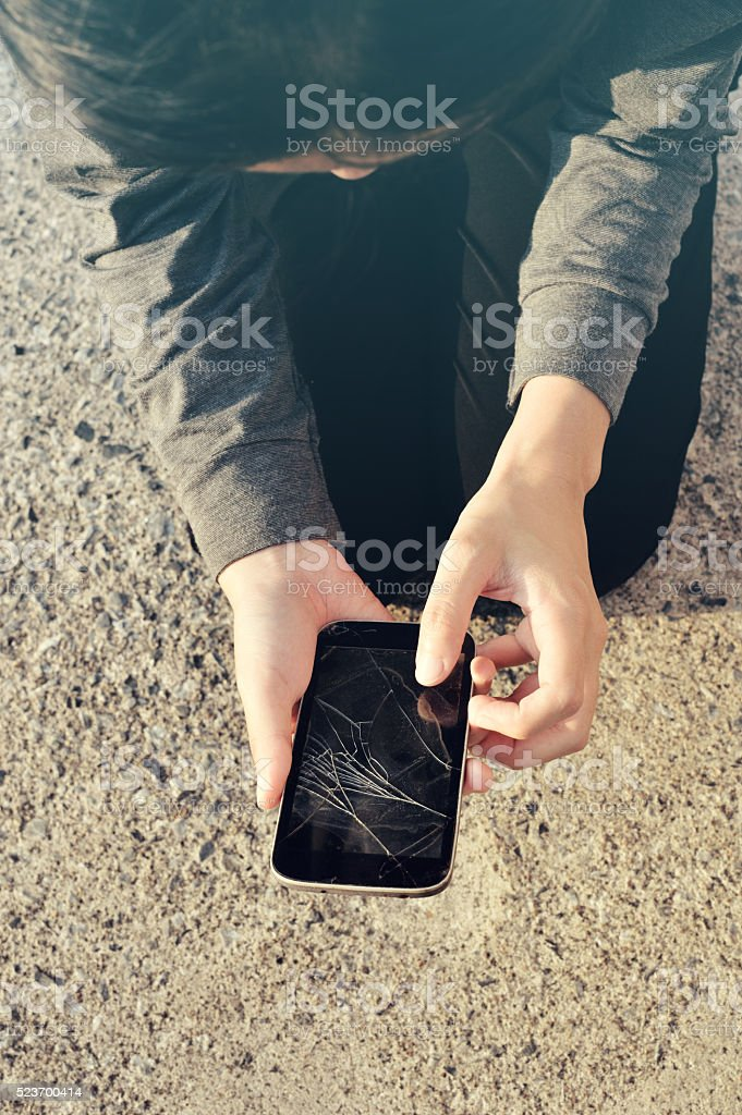Woman with a broken cracked phone screen stock photo